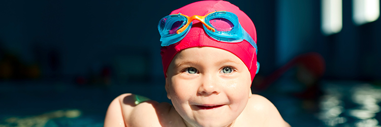 Child in swimming cap with goggles