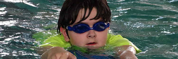 kid wearing goggles swimming in pool