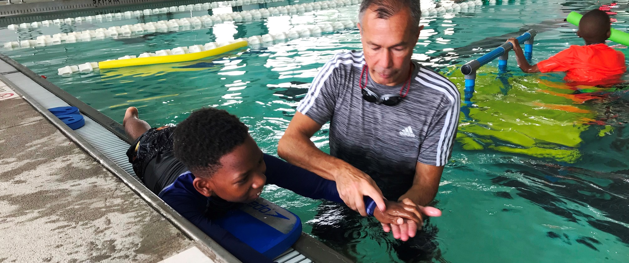 instructor showing child how to swim